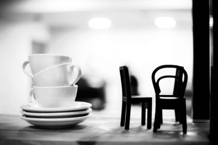 Pile of coffee cups with little chairs on the shelf in cafe. Interior details.