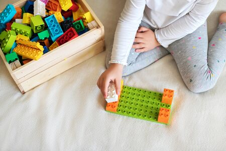 Little girl playing with her colorful blocks in her room.