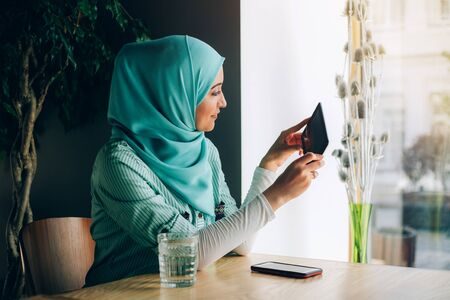 Beautiful young arabic girl in hijab posing for camera at cafe with digital tablet near the window. Stock fotó