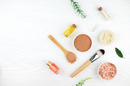 Homemade spa cosmetic set with salt, clay mask and oil on white wooden background. Copy space. Flat lay style.