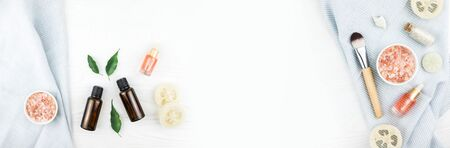 Banner made from homemade spa cosmetic set with salt and oil on white wooden background. Copy space. Flat lay style.