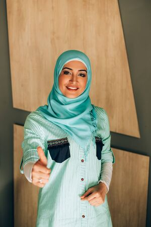 Portrait of pretty young muslim woman against wooden wall. Woman in hijab thumbs up and smiling.