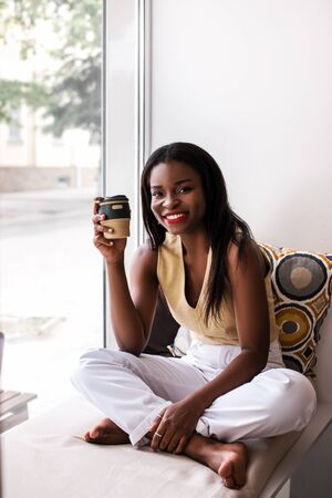 Attractive african girl drinking coffee at the windowsill at cafe by reusable cup of coffee.