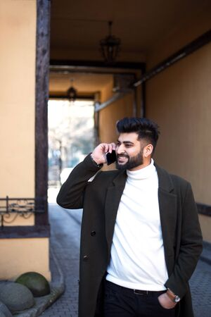 Young Indian businessman talking on smartphone and smiling on the street.