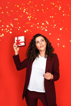 Portrait of young beautiful woman in marsala pantsuit with present box on red background with sparkles.