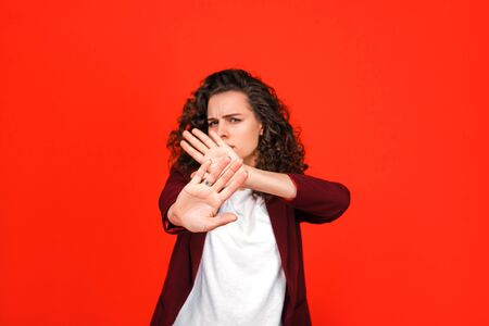 Young woman making stop gesture on red background. She trying protect herself.