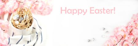 Easter banner with Easter eggs on wooden background. Pink spring flowers on wooden table. Copy space.