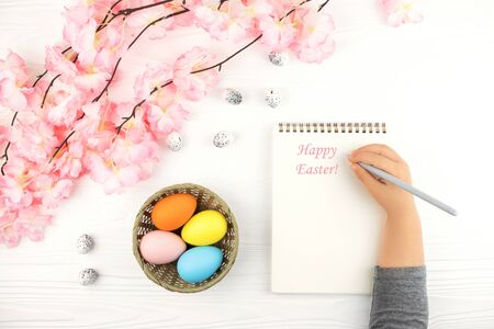 Pastel colored eggs in the nest with the branch of pink flowers on white wooden background. Childs hand with empty notebook on Easter background.