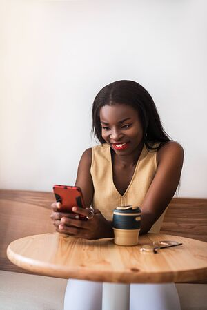 Smiling black girl chatting by smartphone at cafe. She drinks coffee at reusable cup and enjoy good day.