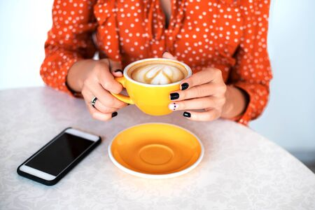 Womans hands with perfect manicure holding cup of coffee in cafe.