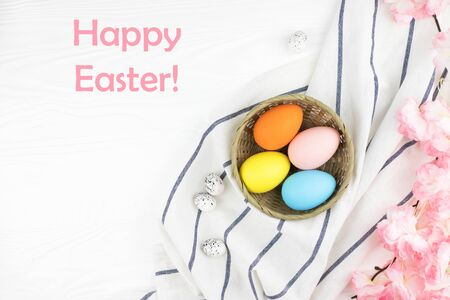 Pastel colored eggs in the nest with the branch of pink flowers on white wooden background. Easter holiday. Text Happy Easter in the corner of picture.