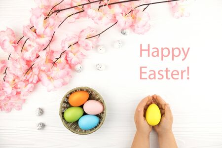 Pastel colored eggs in the nest with the branch of pink flowers on white wooden background. Childs hands holding yellow egg on the Easter background. Text Happy Easter in the corner.