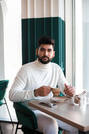 Young indian man drinking coffee in cafe and looking at camera.