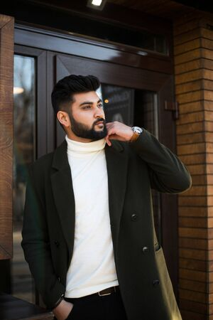 Portrait of fashionable well dressed bearded man at street. Young Indian man in green coat posing outdoors looking away. Stock fotó