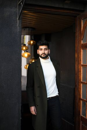 Portrait of fashionable well dressed bearded man at street. Young Indian man in green coat posing outdoors looking away. Фото со стока