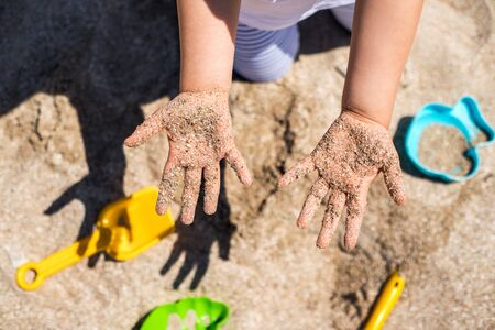 Close up hands of happy girl playing in sand on the beach. Stock Photo