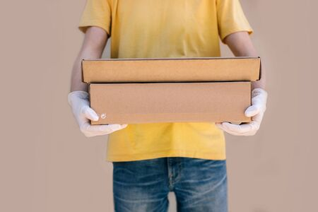Man from delivery service in protective gloves holding box. Isolated on beige background. Фото со стока