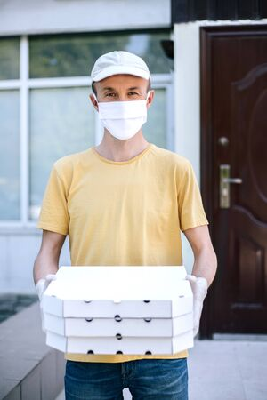 Man from delivery service in protective mask and gloves holding three pizza boxes.