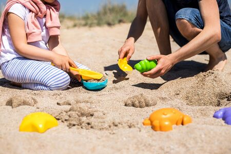 Happy father and daughter play in sand on the beach and have fun together.