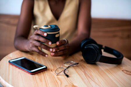 Pretty young black girl listening to music on smartphone at cafe. She drinks fresh hot coffee at reusable cup. Stockfoto