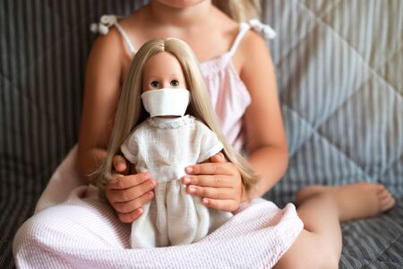 Little girl withholding doll wearing a protective face mask.