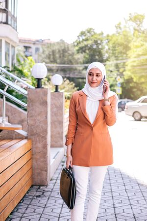 Beautiful young arabic girl in hijab talking by phone at street.