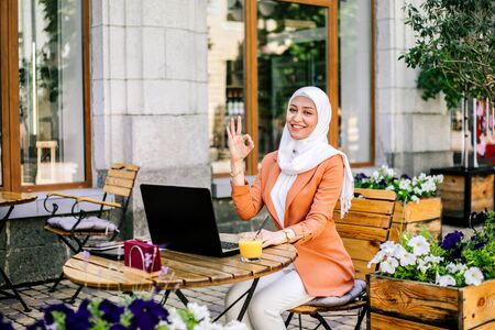 Beautiful young arabic girl in hijab working street cafe at summer. She is making OK gesture and smiling.