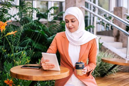 Beautiful young arabic girl in hijab working with her digital tablet at street cafe at summer.