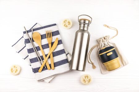 Eco set with bamboo cutlery, reusable coffee mug and water bottle with kitchen towels on white background. Sustainable lifestyle. Zero waste and plastic free concept. Stockfoto