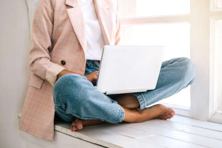 Woman sitting at windowsill and working at laptop. Close up.