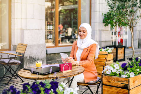 Beautiful young arabic girl in hijab working street cafe at summer.