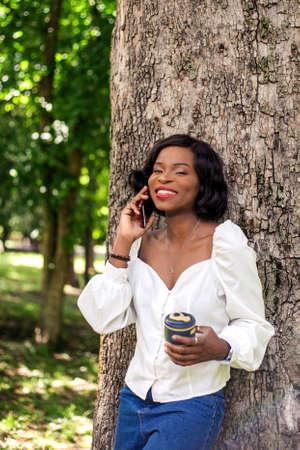 Beautiful african woman talking by phone standing near tree in the park with reusable cup of coffee. Stockfoto