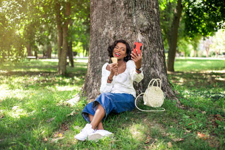 Beautiful african woman making selfie by phone sitting near tree in the park with ice-cream.