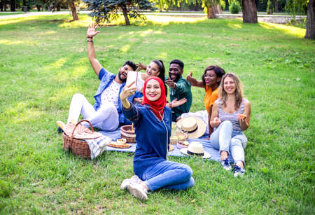 Best multiracial friends are on picnic in the park. One of the friends make selfie by smartphone. Stockfoto