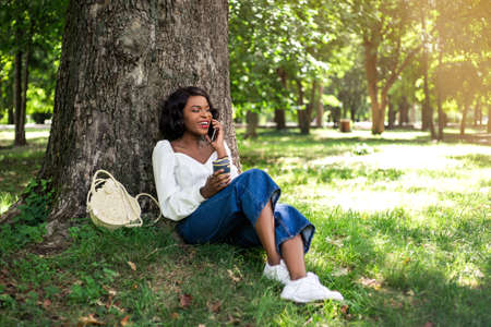 Beautiful african woman talking by phone and sitting on the grass with reusable cup of coffee.