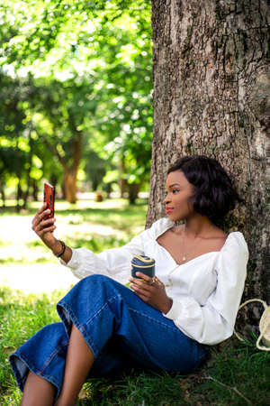 Beautiful african woman making selfie by phone sitting near tree in the park.