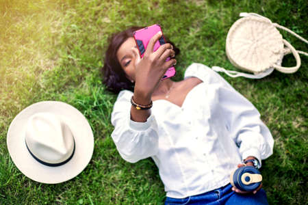 Portrait of beautiful young african woman smiling and using her smartphone while lying on the grass in the park with straw hat, bag and reusable cup of coffee. Stockfoto