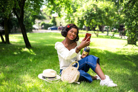 Beautiful african woman making selfie by phone sitting on the grass in the park. Stockfoto