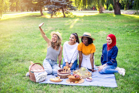 Young multiracial women are on picnic in the park. Best multiracial friends have fun together. Stockfoto