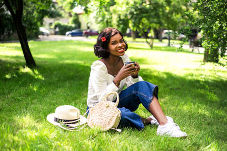 Beautiful african woman enjoing her coffee sitting on the grass with reusable cup of coffee.