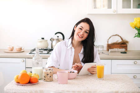 Young beautiful woman using digital tablet while healthy breakfast in light modern kitchen.