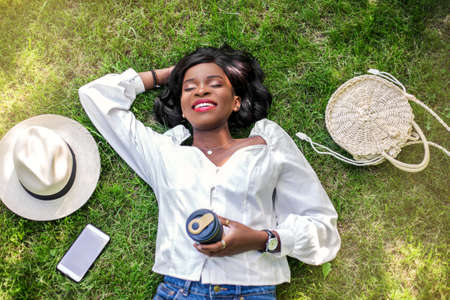 Portrait of beautiful young african woman smiling while lying on the grass in the park with straw hat, bag, phone and reusable cup of coffee.