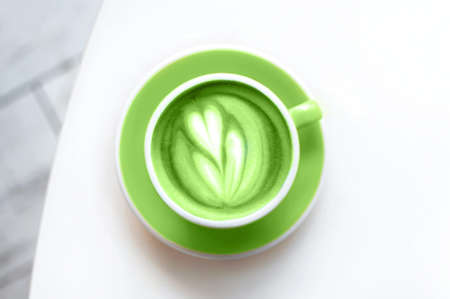Fresh green matcha with frothy foam, green coffee cup top view closeup is on the white background. Flat lay style.