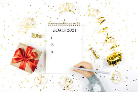 Childs hand writing in notebook on white rustic sparkling background, flat lay style. Christmas planning concept.
