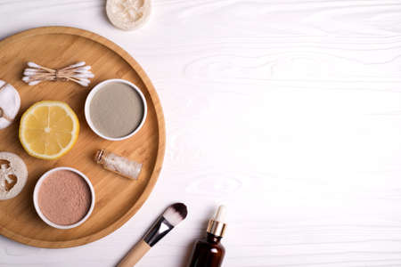 Cosmetic clay facial masks, sea salt, lemon and brush on white wooden background. Flat lay style. Imagens