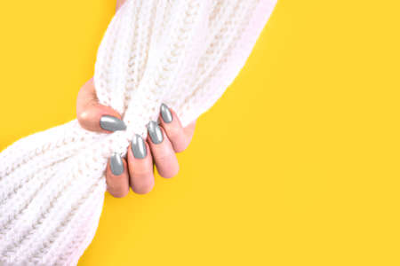 Beautiful art manicure of modern yellow and gray colors background . Nail polish. Fingers holding white wool material sleeve blouse.