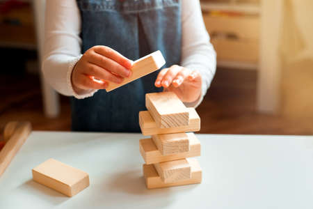 Little girl playing with wooden bricks at home. She builds little tower.