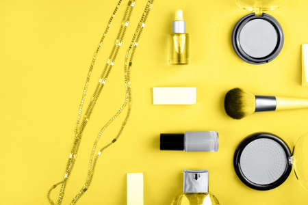 Set of decorative cosmetics for make up on yellow background. Copy space, flat lay.