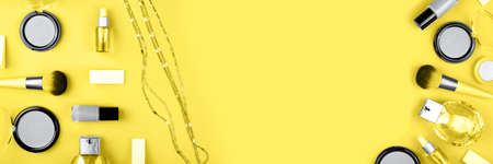 Banner made from set of decorative cosmetics for make up on yellow background. Copy space, flat lay.