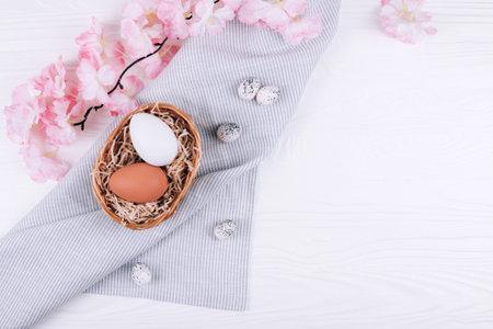 Easter eggs in the nest on textile napkin with sakura blossom on white wooden background.